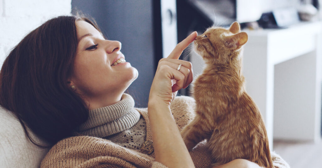 A pet owner plays with her cat.